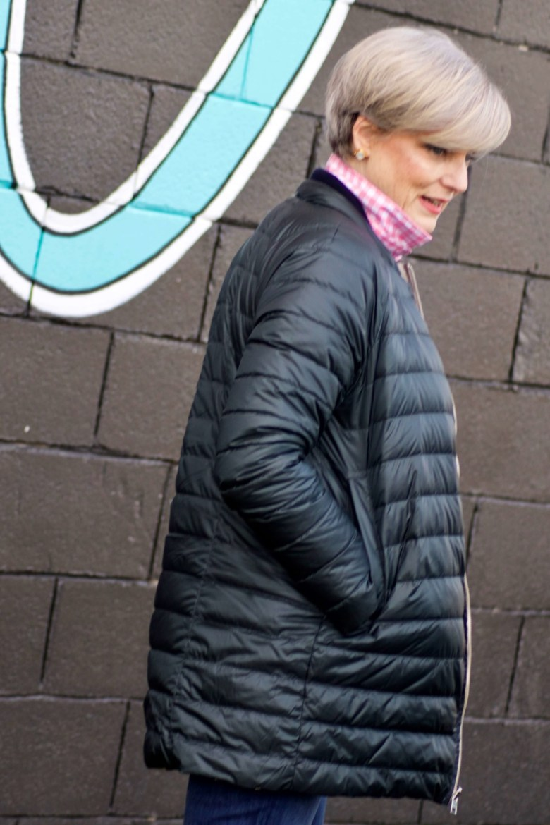 beth from Style at a Certain Age wears a puffer jacket, navy blue knit blazer, novelty sweater, pink gingham check shirt and blue jeans