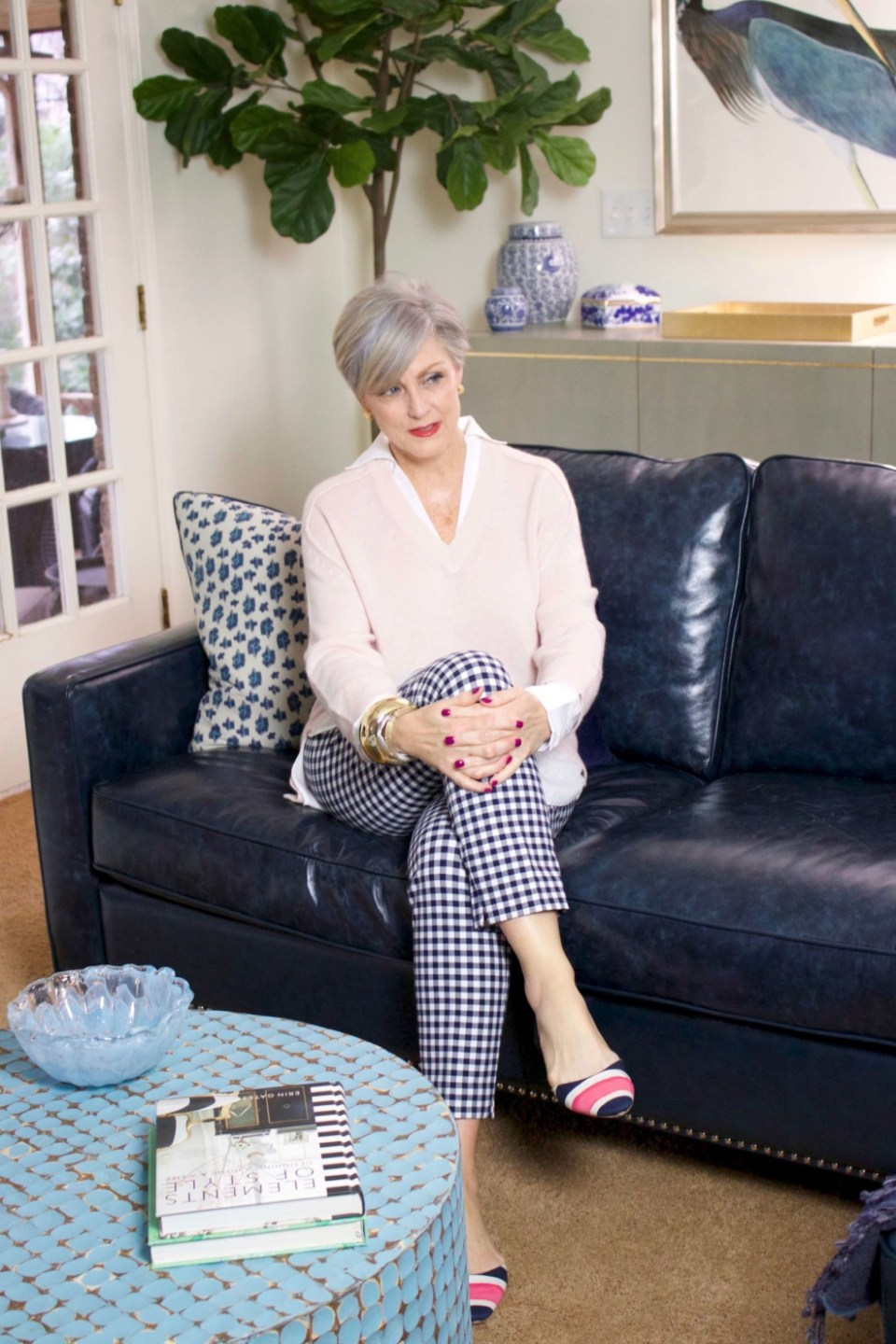 beth from Style at a Certain Age wears a paloma pink sweater with white underlay, gingham pants, and pointy toe flats