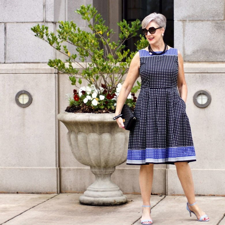 beth from Style at a Certain Age wears a fit and flare dress, kitten heel sandals, and a black clutch handbag