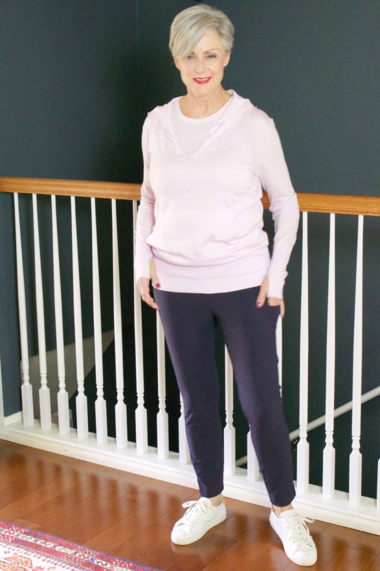 beth from Style at a Certain Age wears travel style Athleta wander slim pants, essence vital tank, and enlighten sweater hoodie