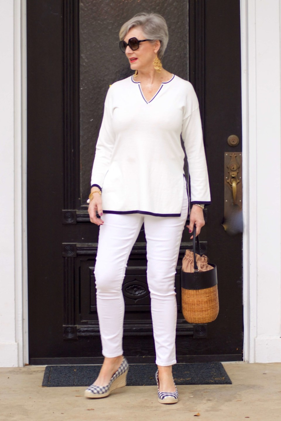 beth from Style at a Certain Age wears a monochromatic white outfit. white tunic trimmed in blue, white jeans and gingham espadrilles