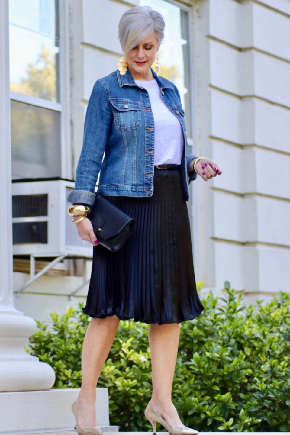 beth from Style at a Certain Age wears a black pleated skirt, white tee, denim jacket, and gold metallic pumps