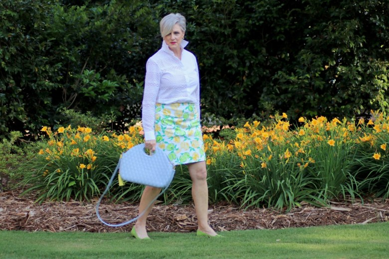beth from Style at a Certain Age wears a lemon print skirt, eyelet blouse, pointy-toed flats and o-bag