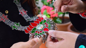 Lotus motif silver haar (long necklace) centered with a hand-painted motif, surrounded with red and green glass work