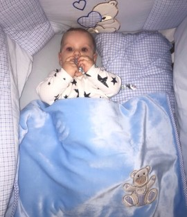 baby lying in bed with pacifer