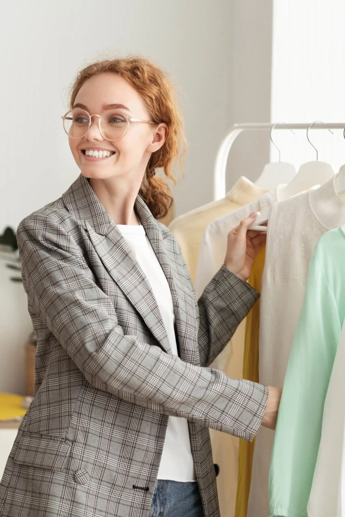 Fashion Closet Concept. Happy stylish girl in glasses choosing designer clothing on hangers, copy space