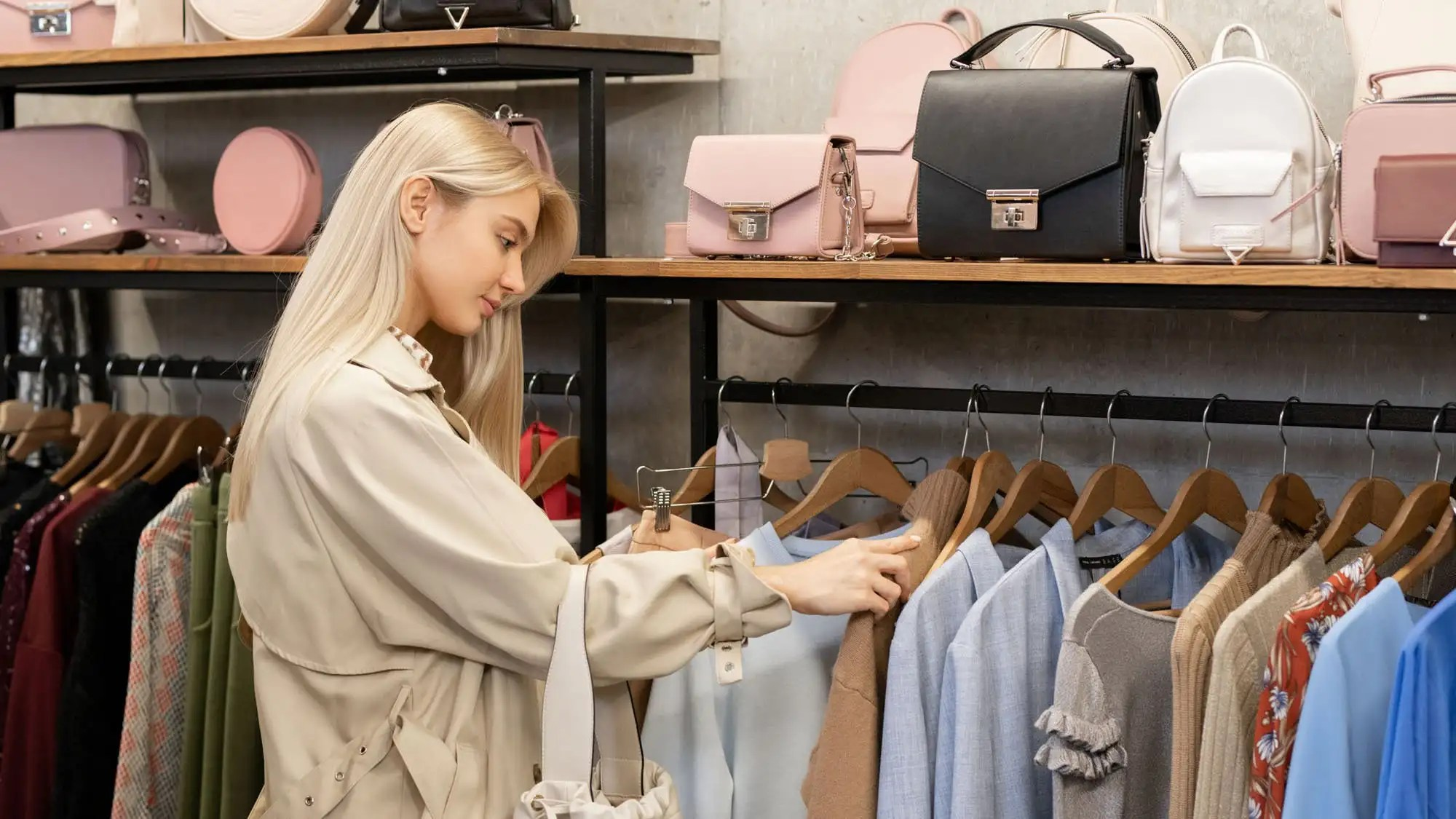 Pretty young female in elegant beige trenchcoat looking through new fashion collection while shopping in boutique