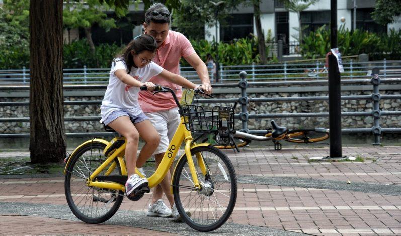 Pai dando apoio à sua filha para andar de bicicleta.
