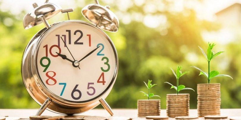 Relógio e moedas demonstrando que a economia cresce, e muito, ao longo do tempo quando decide-se economizar na festa infantil das crianças.