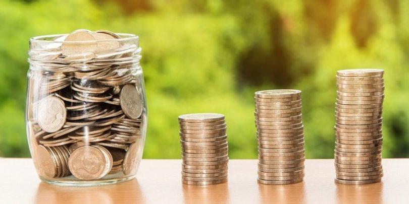 Pote e pilhas de moedas fazendo referência ao pote da harmonia, passo fundamental de como organizar sua vida financeira em casal com qualidade.