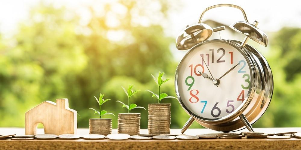 A figura de um imóvel, moedas e um relógio, indicando que investir em imóveis pode ser rentável e leva tempo.