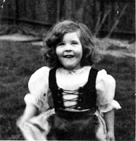 A b&w photo of a young girl in dress-up mediaeval outfit