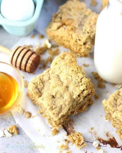 Easy Oatmeal Bars on parchment paper with a honey spoon and bowl next to them.