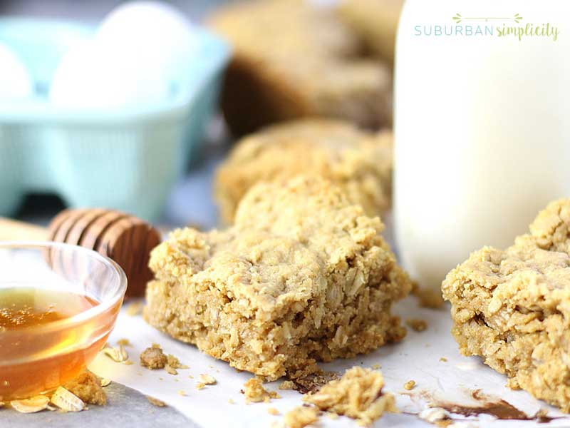 Baked Oatmeal Bars next to a bowl of honey with a glass of milk in the background.
