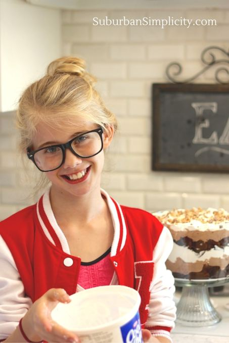Girl with hair in a bun holding Cool Whip with Chocolate Trifle in the backdrop.