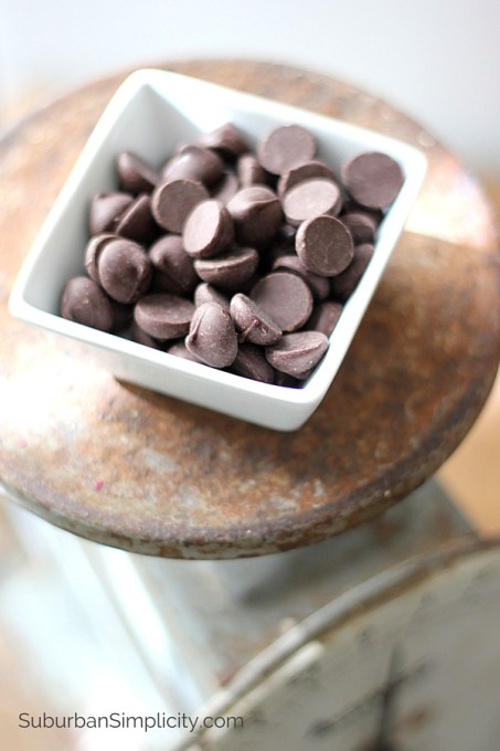 Dark Chocolate Chips sitting in a square white bowl atop a vintage scale.