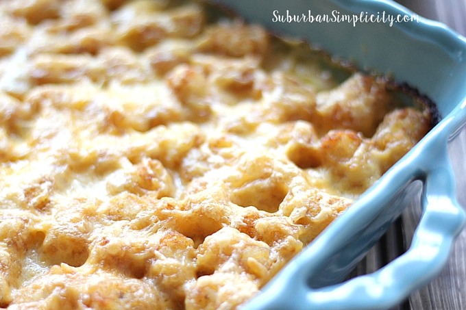 Tater tot casserole in a blue casserole pan with melted cheese on top.
