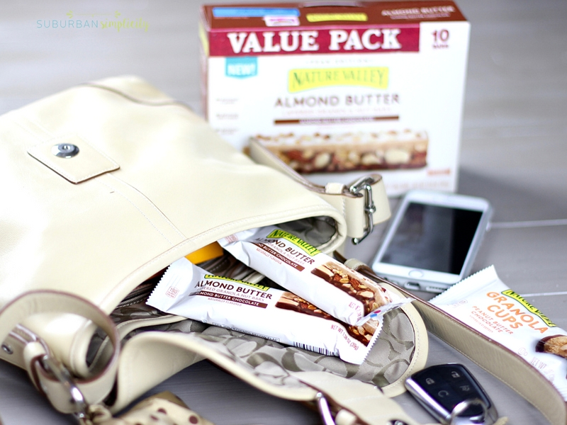 Purse with granola bars, phone and other essentials on a table.