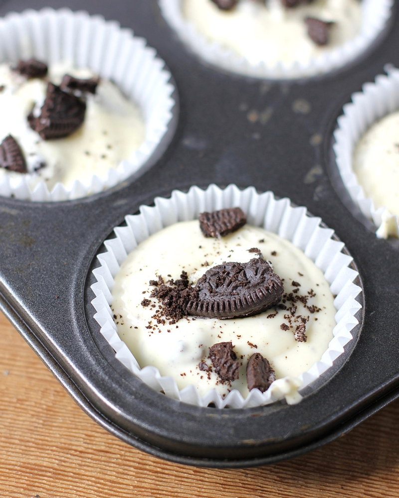 Muffin tins filled with Oreo Cheesecake and topped with bits of Oreo Cookie.