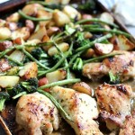 Delicious chicken and veggies roasted in the oven on a pan.