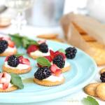 Plate full of crackers topped with berries and cream.