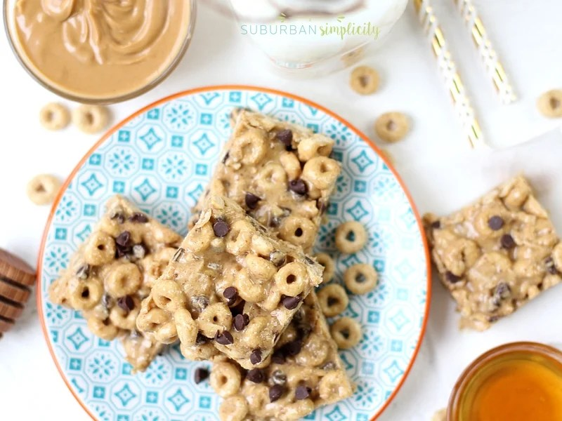 Honey Nut Cheerios protein bites on a plate with peanut butter in the background