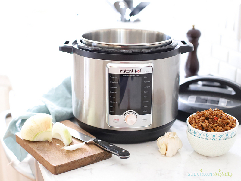 Instant pot on the counter with ingredients to make dinner.