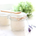 Jar of the best sugar scrub with a wooden spoon on top.
