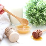 A wooden spoon in a bowl of milk and honey sugar scrub.
