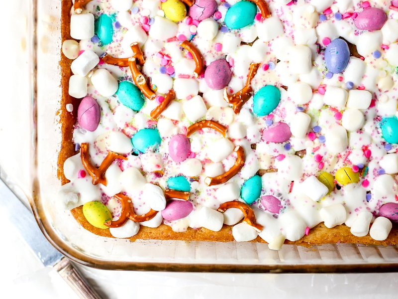 Spring Confetti Cookies Bars are the perfect Easter dessert recipe! Sugar cookie dough topped with fluffy marshmallows, spring candy and salty pretzels.