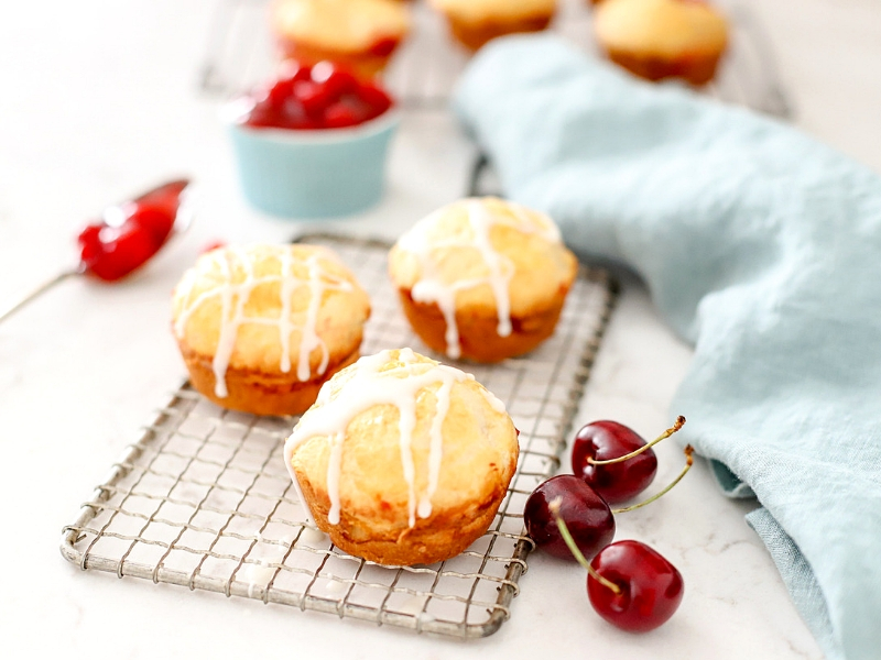 Cherry Pie Bombs with vanilla drizzle on counter.
