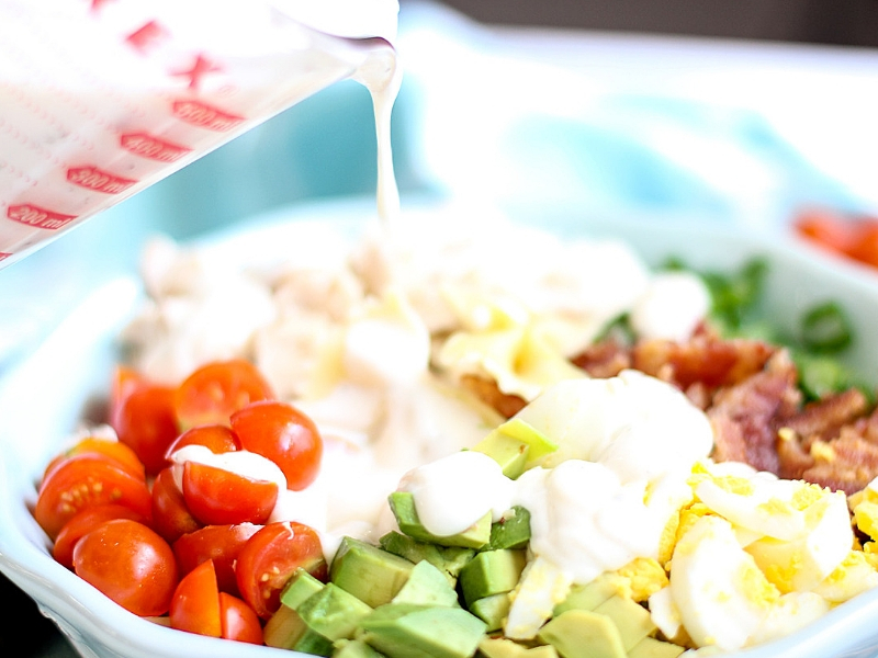 Cobb Pasta Salad with dressing being poured over it.