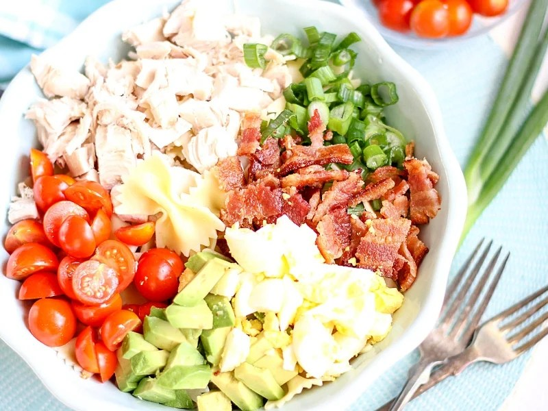 Ingredients for a Cobb Pasta Salad in a bowl.