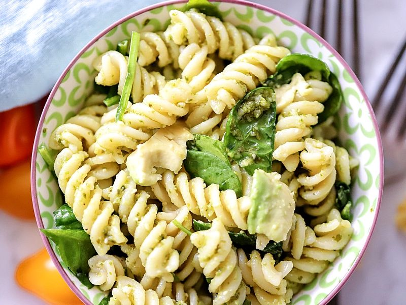 Pasta in a bowl with pesto, spinach and avocado.