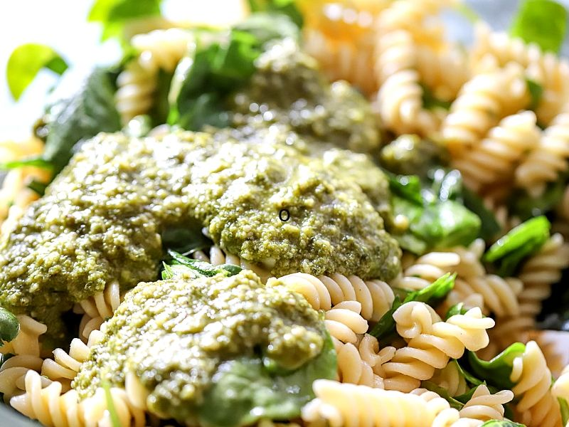 Basil pesto being mixed in a bowl with pasta.