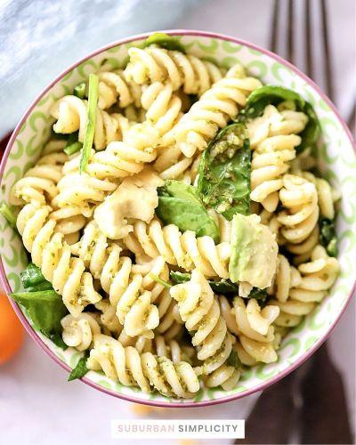 Close up photo of pesto pasta in a bowl.