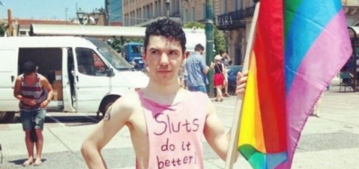 Zak Kostopoulos in the street with a Pride Flag