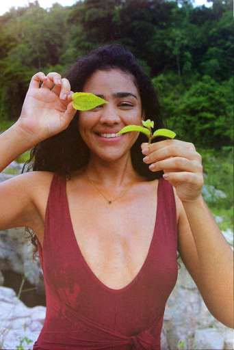 Karlia holding a leaf at El Sofa River in Puerto Rico for feminine care brand Momotaro Apotheca.