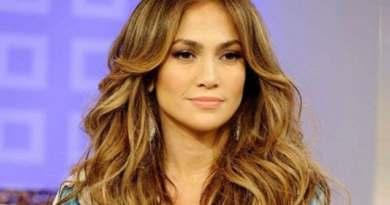 J.Lo la cantante de 51 años luciendo un espectacular peinado y una bella sonrisa, en una alfombra roja.