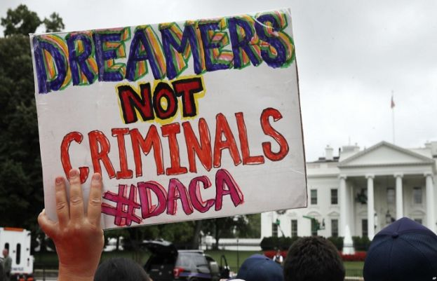 A woman holds a sign in support of Deferred Action for Childhood Arrivals, or DACA, during an immigration reform rally at the White House in Washington, Aug. 15, 2017.