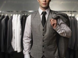 Businessman wearing classic vest against row of suits in shop