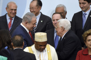 """Israeli Prime Minister Benjamin Netanyahu, center left, talks with Palestinian President Mahmoud Abbas, center right, as they wait to pose for a group photo as part of the COP21, the United Nations Climate Change Conference, in Le Bourget, outside Paris, Monday, Nov. 30, 2015. More than 150 world leaders are meeting under heightened security, for the 21st Session of the Conference of the Parties to the United Nations Framework Convention on Climate Change (COP21/CMP11), also known as """"Paris 2015"""" from November 30 to December 11. (Martin Bureau/Pool Photo via AP)"""