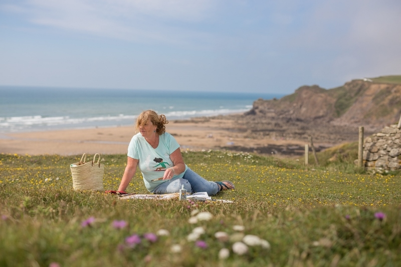 Cornish artist painting on the coast
