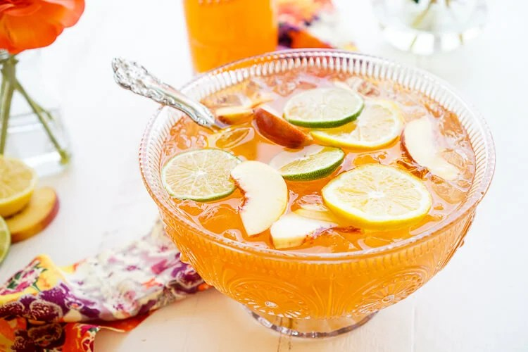This SpikedPeach Punch is the perfect big batch cocktail for summer! Smooth Alizé Peach vodka blends with white rum, lime juice, and ginger ale for a refreshing and vibrant warm weather beverage!