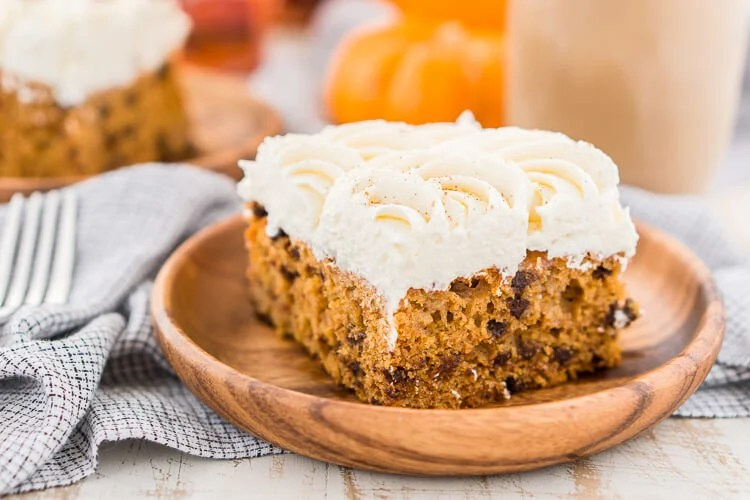 This Pumpkin Chocolate Chip Poke Cake is a deliciously seasonal dessert that's great for potlucks and family gatherings. A dense pumpkin spice cake soaked in sweetened condensed milk and loaded with chocolate chips is topped with a fluffy cheesecake frosting and dusted with cinnamon!