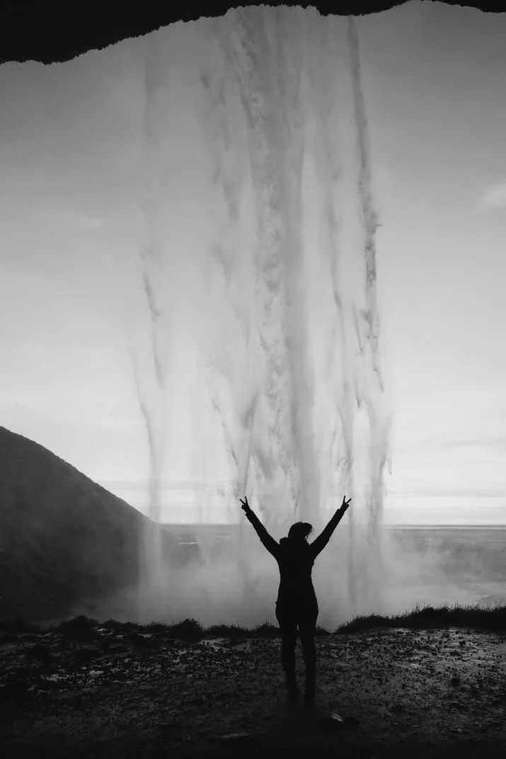 Girl under waterfall in Iceland