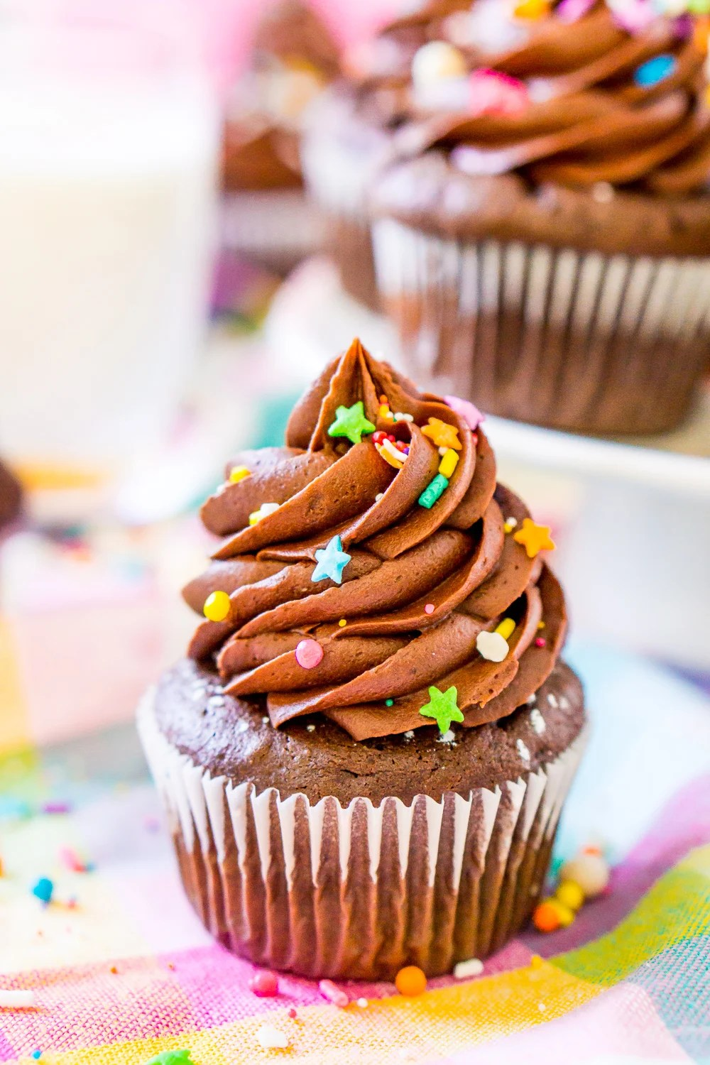 Chocolate Cupcake on colorful napkin with a white cake stand with more chocolate cupcakes in the background.