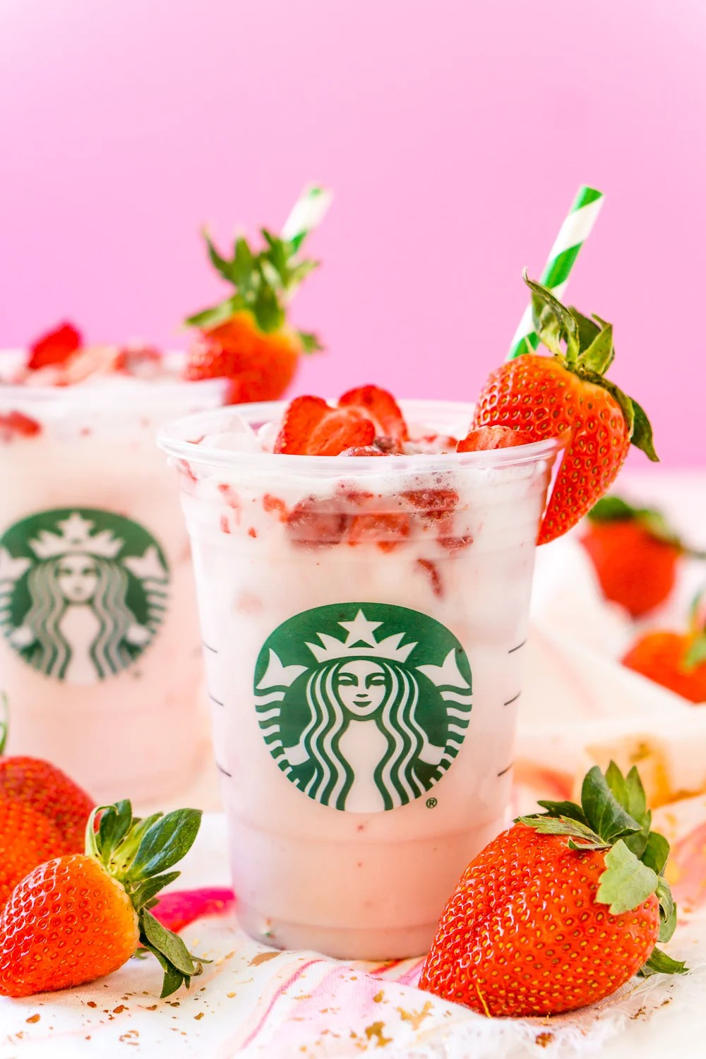 Copycat Starbucks Pink Drink in clear Starbucks cup with strawberries and pink background.
