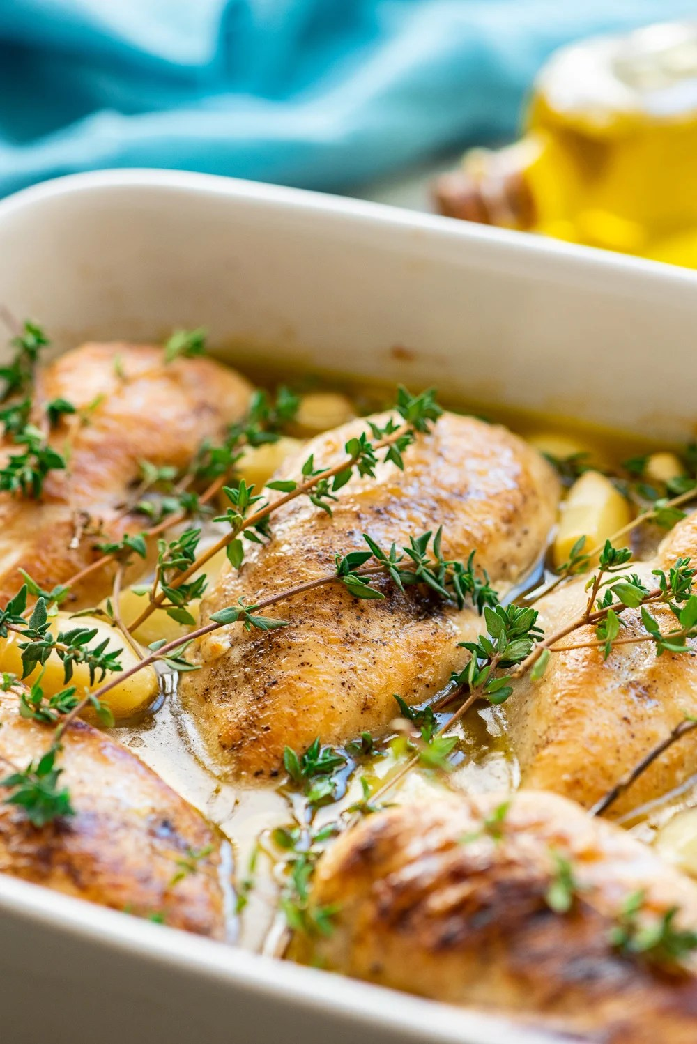 Baked Garlic Chicken in baking dish with thyme and garlic cloves.