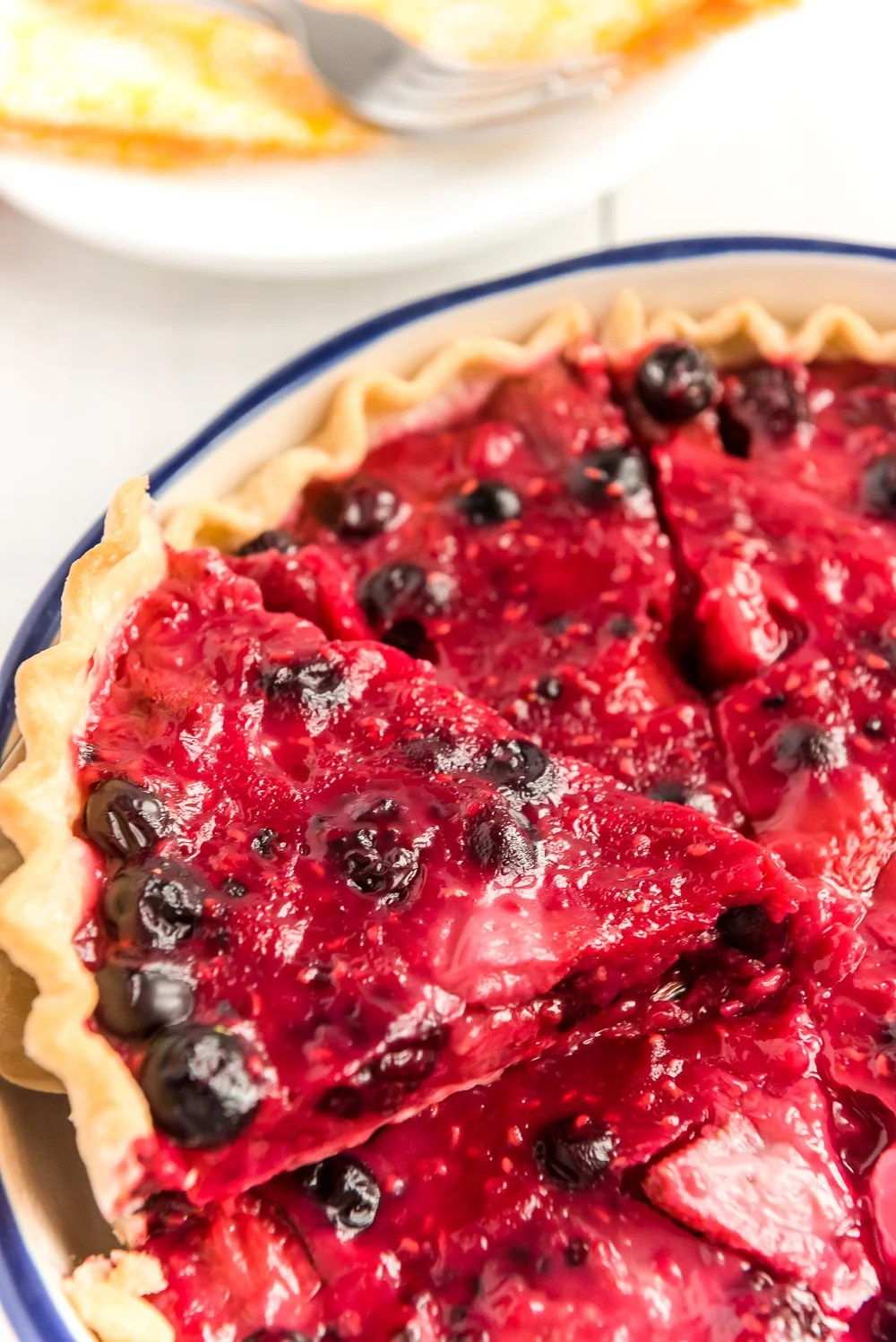Slice of Mixed Berry Pie being pulled from a whole pie.